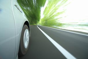 新緑の中を走るハイブリッドカーのタイヤの写真素材 [FYI04203009]