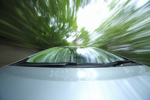 新緑の中を走るハイブリッドカーの写真素材 [FYI04203010]