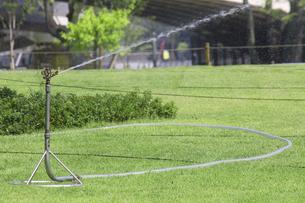 公園の芝生に散水する自動散水機の写真素材 [FYI04206544]