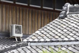 日本家屋の屋根に設置されたエアコン室外機の写真素材 [FYI04206695]