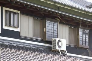 日本家屋の屋根に設置されたエアコン室外機の写真素材 [FYI04206696]
