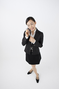 携帯電話で会話をするOLの写真素材 [FYI04208504]