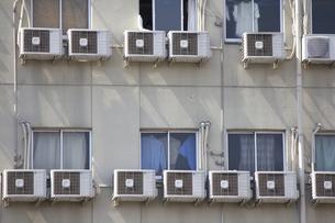 ワンルームマンションの壁に並んだたくさんのエアコン室外機の写真素材 [FYI04218708]