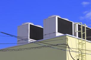 倉庫の屋根のエアコン室外機と青空の写真素材 [FYI04218966]