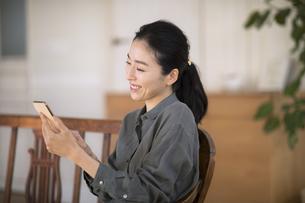 部屋でスマートフォンを手に微笑む女性の写真素材 [FYI04238236]