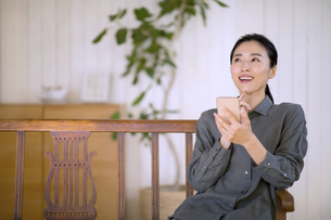 部屋でスマートフォンを手に考える女性の写真素材 [FYI04238282]