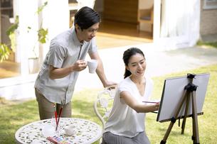 庭で絵を描く女性と絵を見る男性の写真素材 [FYI04238306]