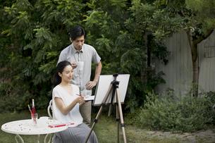 庭で絵を描く女性と絵を見る男性の写真素材 [FYI04238307]