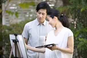 庭で絵を描く女性と絵を見る男性の写真素材 [FYI04238407]