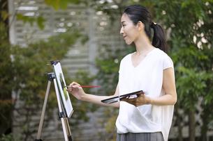 庭で絵を描く女性の写真素材 [FYI04238409]