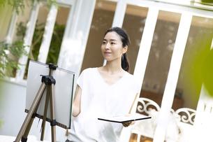 庭で絵を描く女性の写真素材 [FYI04238432]
