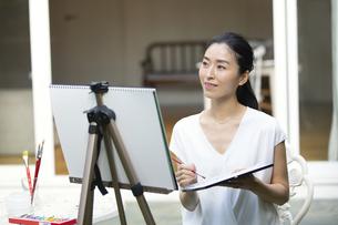 庭で椅子に座り絵を描く女性の写真素材 [FYI04238513]