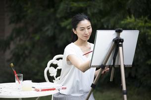庭で椅子に座り絵を描く女性の写真素材 [FYI04238514]