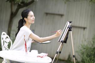 庭で椅子に座り絵を描く女性の写真素材 [FYI04238537]
