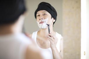 鏡を見ながら髭を剃る男性の写真素材 [FYI04238585]