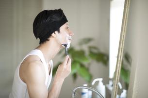 鏡を見ながら髭を剃る男性の写真素材 [FYI04238606]