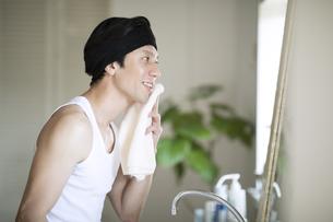 タオルを顔にあて鏡を見る男性の写真素材 [FYI04238609]