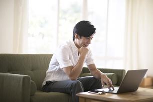 ソファーでノートパソコンを操作する男性の写真素材 [FYI04238664]