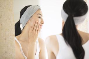 鏡越しに頬に手を当てる女性の写真素材 [FYI04238708]
