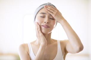 頬と額に手をあてて目を瞑る女性の写真素材 [FYI04238709]