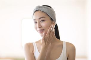 コットンを頬に当てる女性の写真素材 [FYI04238775]