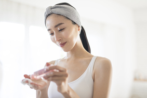 化粧水をコットンに染み込ませる女性の写真素材 [FYI04238788]
