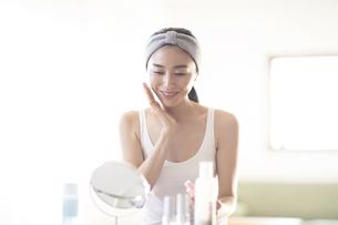 メイク中に化粧水を頬にあてる女性の写真素材 [FYI04238800]