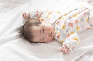 明るい部屋の中でぐっすりと眠るかわいい赤ちゃんの写真素材 [FYI04243190]
