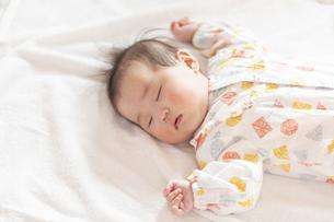 明るい部屋の中でぐっすりと眠るかわいい赤ちゃんの写真素材 [FYI04243210]