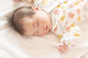 明るい部屋の中でぐっすりと眠るかわいい赤ちゃんの写真素材 [FYI04243211]