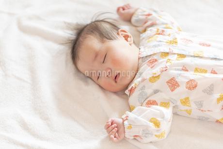 明るい部屋の中でぐっすりと眠るかわいい赤ちゃんの写真素材 [FYI04243213]