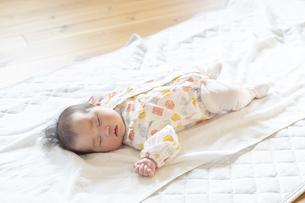 明るい部屋の中でぐっすりと眠るかわいい赤ちゃんの写真素材 [FYI04243239]