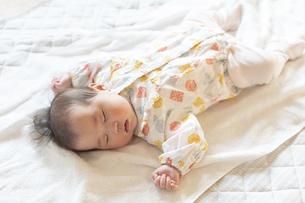 明るい部屋の中でぐっすりと眠るかわいい赤ちゃんの写真素材 [FYI04243243]