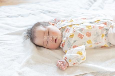 明るい部屋の中でぐっすりと眠るかわいい赤ちゃんの写真素材 [FYI04243264]