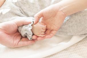 明るい部屋の中で赤ちゃんの手を握る母親の手の写真素材 [FYI04243328]