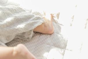 明るい部屋の中で寝転ぶ赤ちゃんの足の写真素材 [FYI04243363]