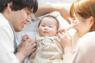 赤ちゃんを中心に寝転ぶ幸せそうな父と母の写真素材 [FYI04243433]