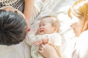 赤ちゃんを中心に寝転ぶ幸せそうな父と母の写真素材 [FYI04243435]