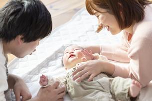 赤ちゃんを中心に寝転ぶ幸せそうな父と母の写真素材 [FYI04243461]