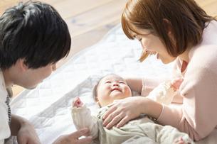 赤ちゃんを中心に寝転ぶ幸せそうな父と母の写真素材 [FYI04243462]