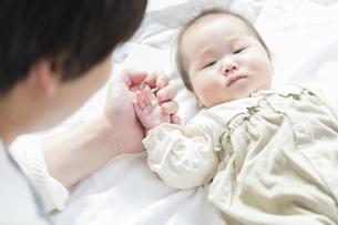 明るい部屋の中で赤ちゃんをあやすお父さんの写真素材 [FYI04243541]