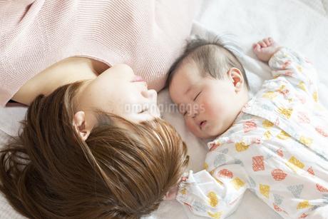 明るい部屋の中で赤ちゃんと一緒に寝るお母さんの写真素材 [FYI04243553]
