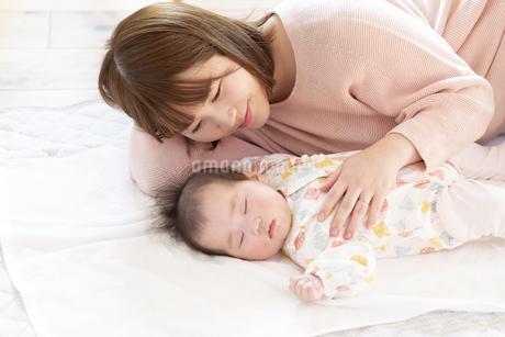 明るい部屋の中で赤ちゃんと一緒に寝るお母さんの写真素材 [FYI04243609]