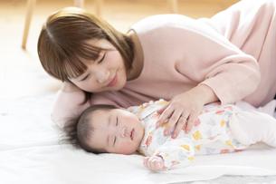 明るい部屋の中で赤ちゃんと一緒に寝るお母さんの写真素材 [FYI04243612]