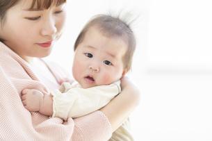 明るい部屋の中で赤ちゃんを抱っこするお母さんの写真素材 [FYI04243669]