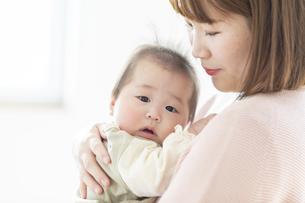 明るい部屋の中で赤ちゃんを抱っこするお母さんの写真素材 [FYI04243671]
