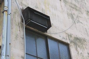 建物の外壁に設置した古いエアコンの室外機の写真素材 [FYI04246017]