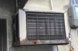 建物の外壁に設置した古いエアコンの室外機の写真素材 [FYI04246018]