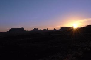 朝日に照されだした荒野とモニュメントのシュルエットのイラスト素材 [FYI04254280]