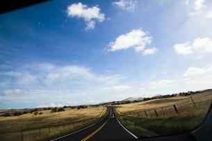 青空の下まっすぐに続くアスファルトの道のイラスト素材 [FYI04254614]